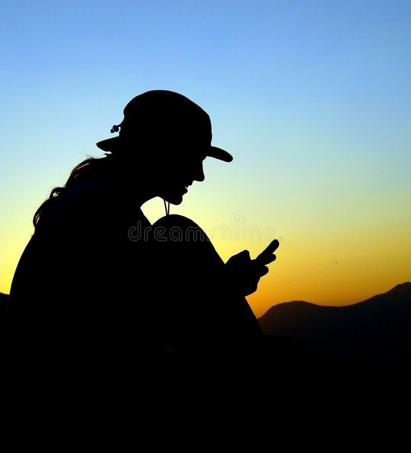 Mann mit Telefon auf dem Berg stockfotografie