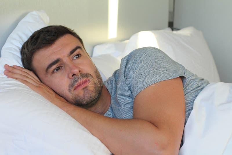 Mann mit traurigem Ausdruck im Bett stockfotografie