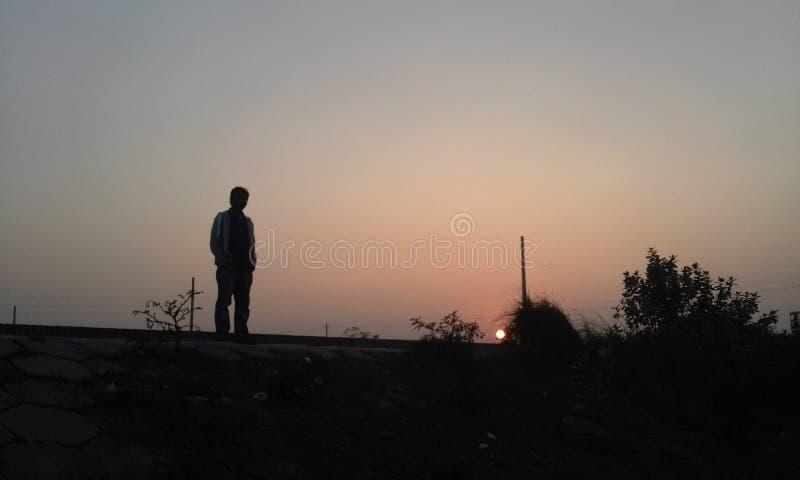 Mann mit untergehender Sonne lizenzfreie stockbilder