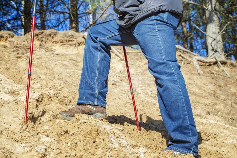 Mann mit Wanderstöcken steigernd zum Hügel stockfoto