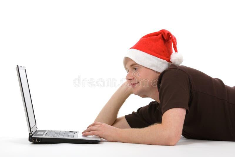 Mann mit Weihnachtshut und -laptop stockfoto