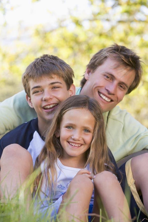 Mann mit zwei Kindern, die draußen lächeln sitzen lizenzfreie stockbilder