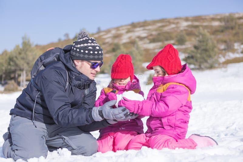 Mann mit zwei Mädchen, die Schneeball machen stockbild