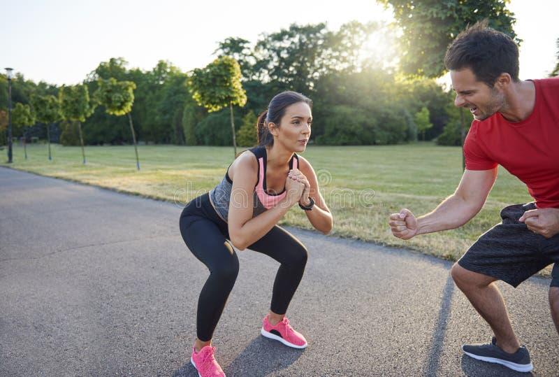 Mann motiviert Frau während des harten Trainings stockbilder