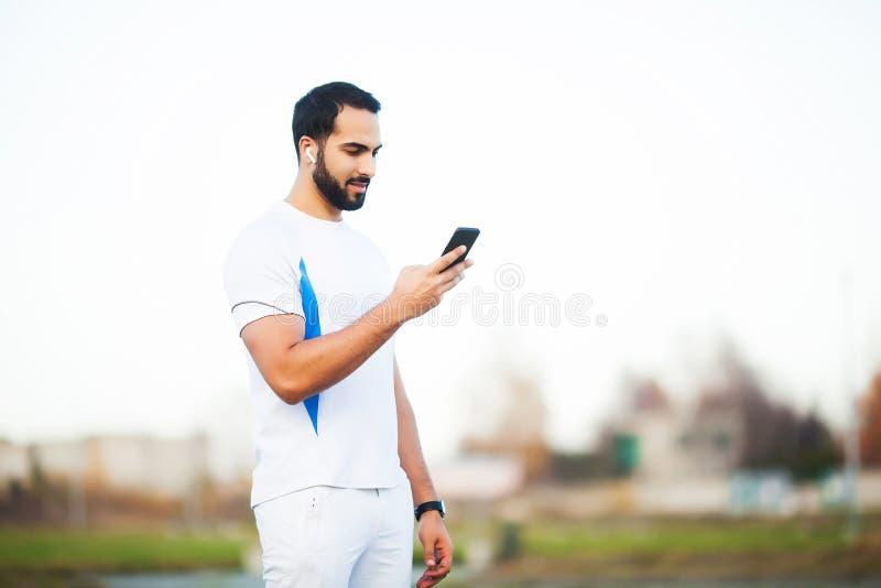Mann nach dem Ausarbeiten im Stadtpark und der Anwendung seines Handys stockfotos