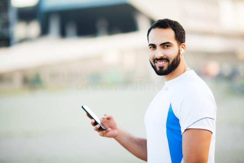 Mann nach dem Ausarbeiten im Stadtpark und der Anwendung seines Handys stockbild