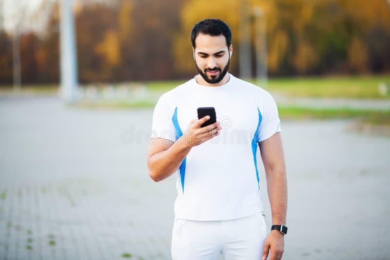 Mann nach dem Ausarbeiten im Stadtpark und der Anwendung seines Handys stockbilder