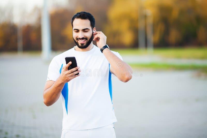 Mann nach dem Ausarbeiten im Stadtpark und der Anwendung seines Handys lizenzfreies stockfoto