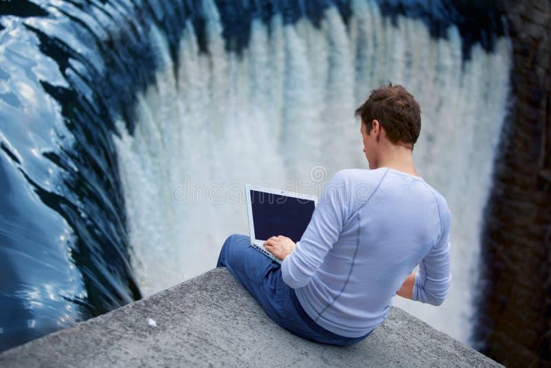 Mann + Notizbuch, das über dem Wasserfall sitzt