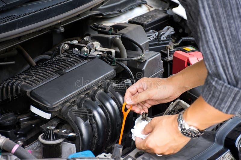 Mann- oder Automechanikerarbeitskrafthände, die das Automotormotoröl und -wartung bevor dem Reisen auf Sicherheit überprüfen stockbilder