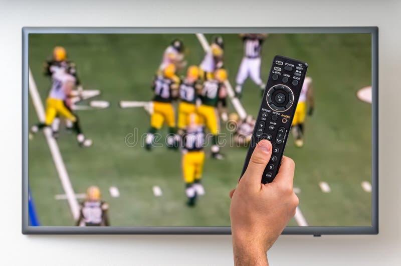 Mann passt Rugbymatch im Fernsehen auf stockfotografie