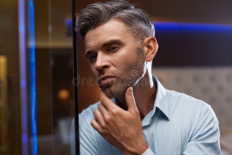 Mann-Pflegen Gut aussehender Mann mit Bart-rührendem Gesicht Zutreffen des transparenten Lacks lizenzfreies stockbild