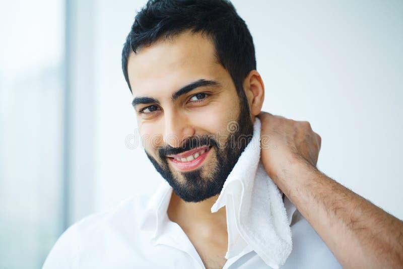 Mann-Reinigungs-Gesichts-Haut mit weißem Tuch lizenzfreie stockfotografie