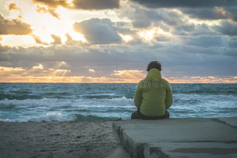 Mann-Reisender, der sich allein auf Strandküste entspannt stockfotos