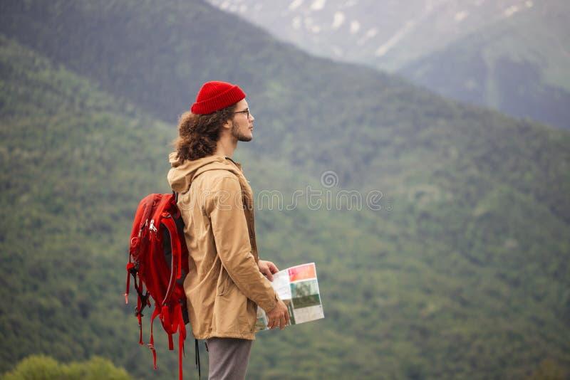 Mann-Reisender mit der Karte und rotem Rucksack, die den Standort im Freien mit felsigen Bergen auf Hintergrund sucht lizenzfreies stockfoto