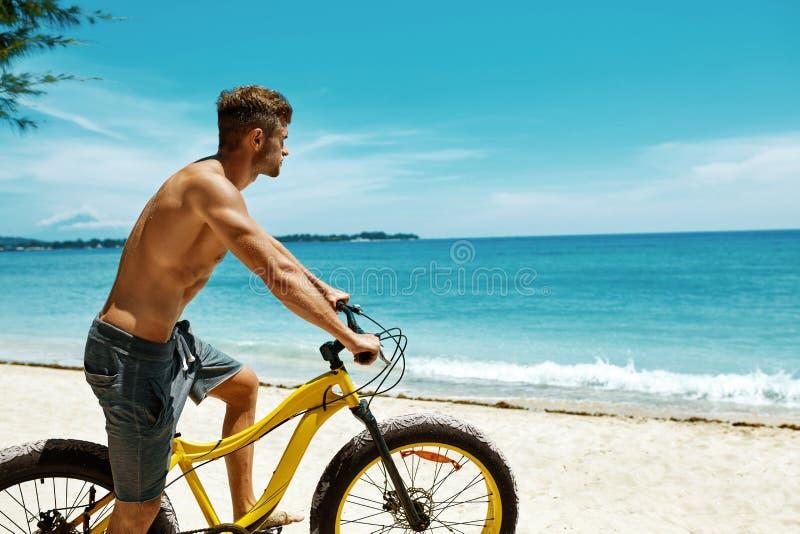 Mann-Reitsand-Fahrrad auf Strand Sommer-Sport-Tätigkeit stockbild