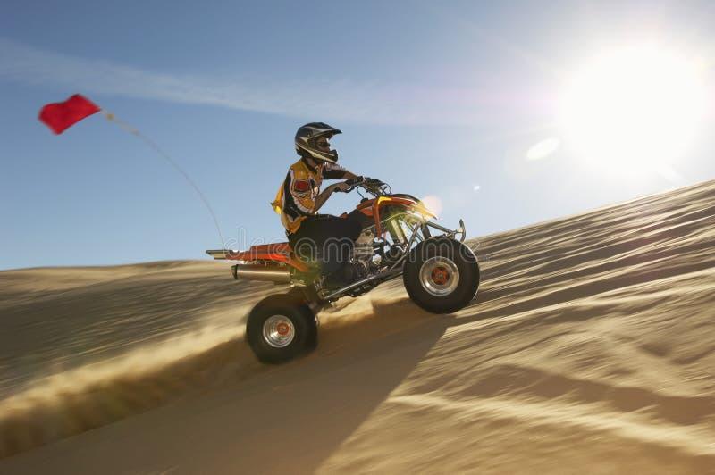 Mann-Reitviererkabel-Fahrrad in der Wüste stockbild