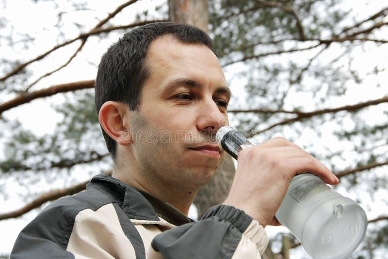 Mann riecht eine Flasche mit Alkoholiker stockfotografie