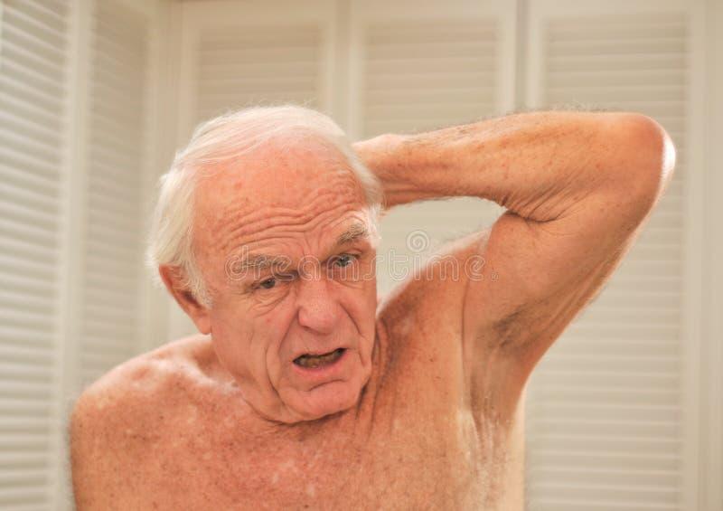 Mann riecht seine Armgrube und reagiert lizenzfreie stockfotografie