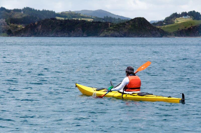 Mann rudert einen Seekajak stockfoto