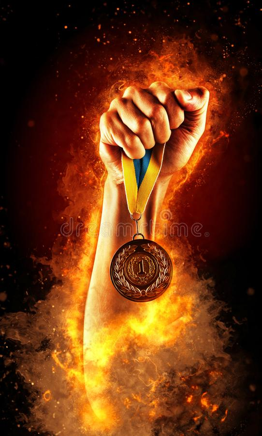 Mann ` s Hand in einem Feuer hält Goldmedaille Sieger in einem Wettbewerb lizenzfreie stockbilder