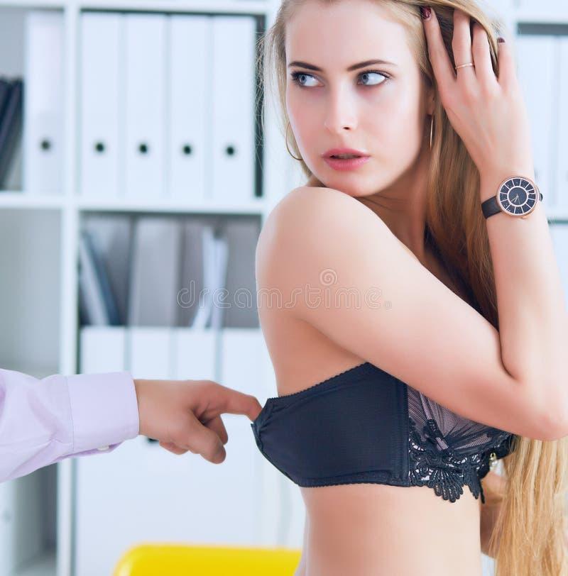 Mann ` s Hand zieht BH den beauitiful Sekretär im Bürohintergrund heraus Flirt oder Belästigungskonzept lizenzfreies stockfoto