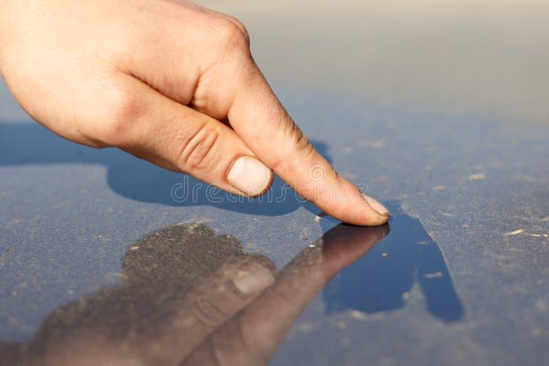 Mann ` s schmutzige Hand wischt Oberfläche von Autoabdeckungen mit Schicht des waschenden Servicekonzepts Staub Autos ab reinigun lizenzfreies stockfoto