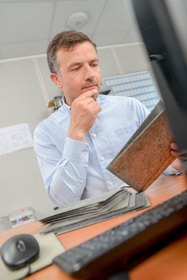 Mann saß am Schreibtisch, der alte Dateien betrachtet lizenzfreies stockfoto