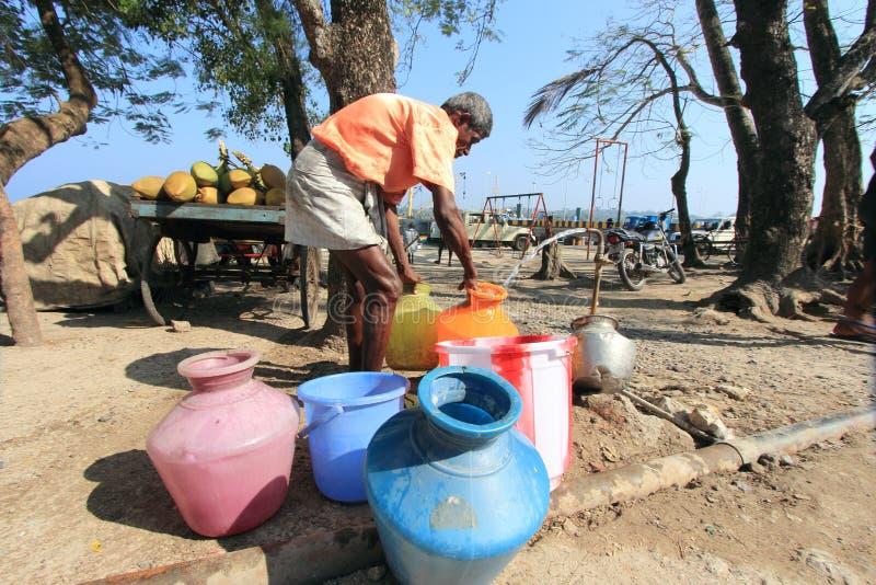 Mann sammelt Trinkwasser in Adamans lizenzfreies stockbild