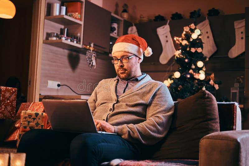 Mann in Sankt-Hut und -gläsern kleidete in der warmen Strickjacke an, die an Laptop am Weihnachten arbeitet stockbild