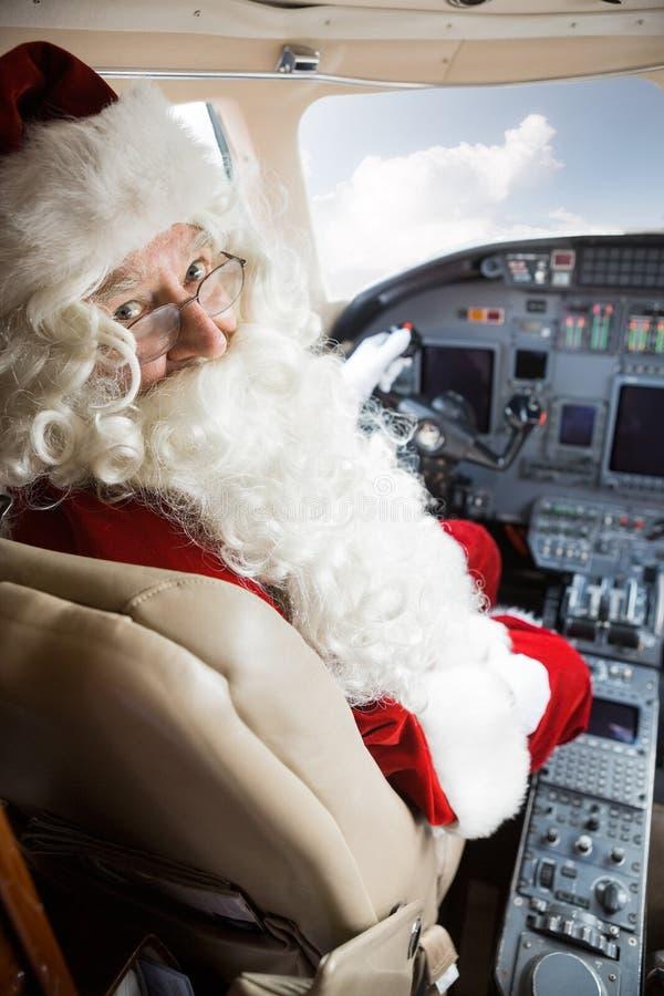 Mann in Santa Costume Sitting In Private-Jet stockbilder