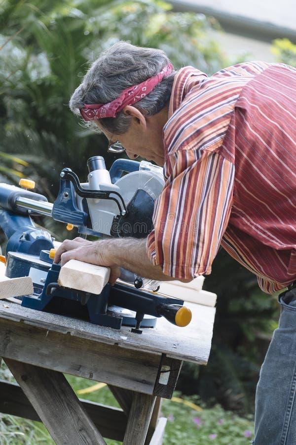 Mann Sawing-Holz mit dem Schieben der Verbundgehrungsfuge sah stockfoto