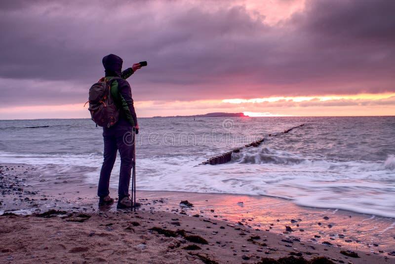 Mann schaut über der Seebucht und genießt wilde Natur Ein Mann bewundert die Schönheit der Naturkraft lizenzfreies stockbild