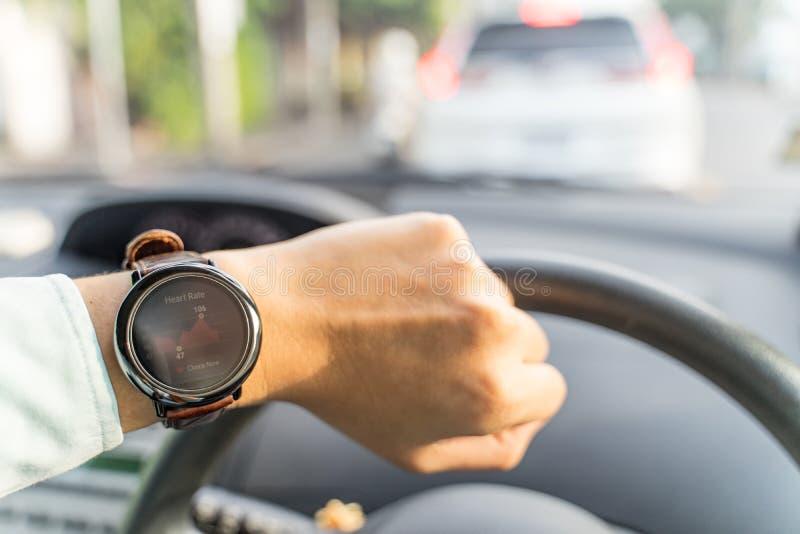 Mann schaut das smartwatch, das Zeitkalorienabstand Pedometer im Auto mit Stau zeigt lizenzfreie stockfotografie