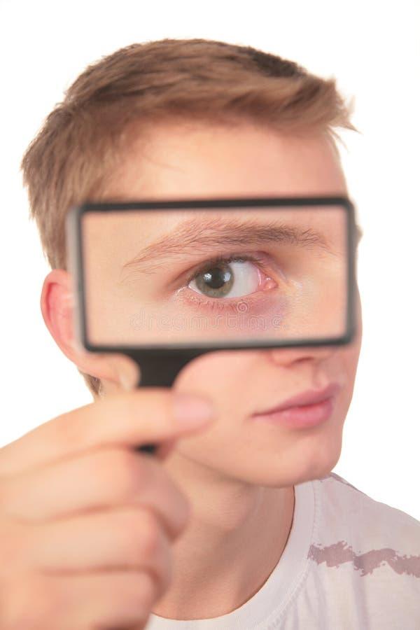 Mann schaut durch Vergrößerungsglas stockbild