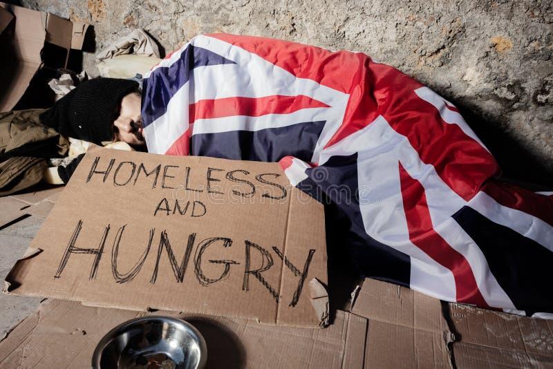 Mann schläft auf Straße unter Flagge von Großbritannien lizenzfreie stockbilder