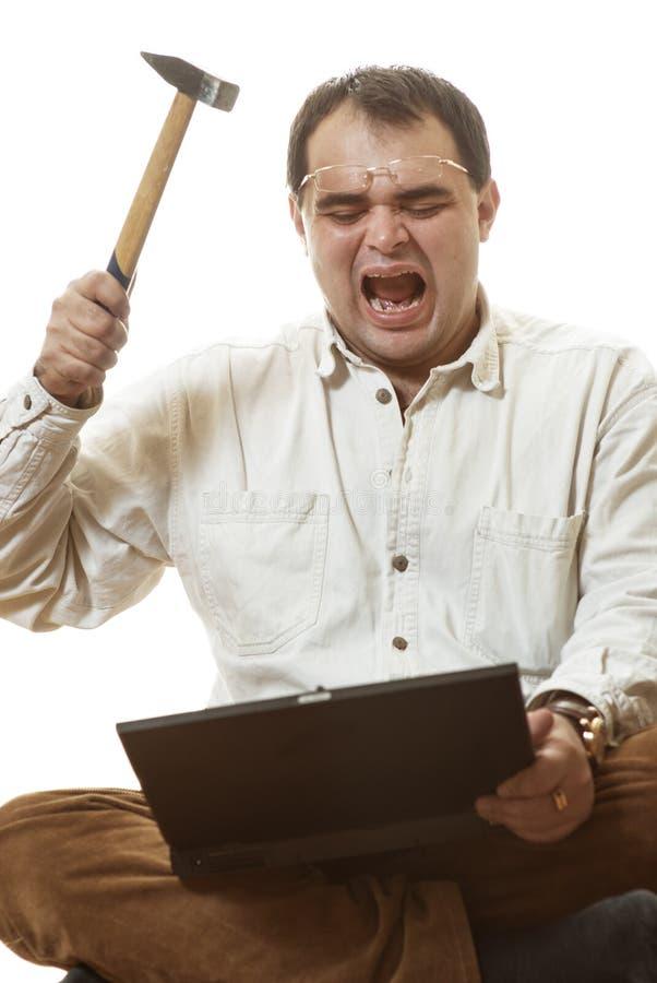 Mann schlägt Hammer auf Laptop lizenzfreies stockbild