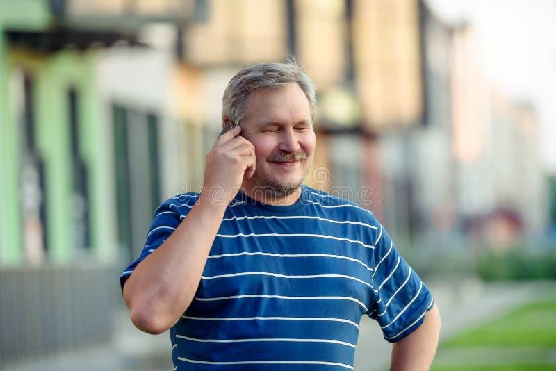 Mann schloss glücklich seine Augen, die auf einem Smartphone auf der Straße sprechen lizenzfreie stockfotos