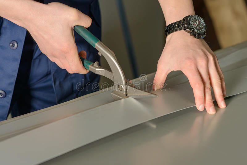 Mann schneidet Blechtafel mit einem Schneider stockbild