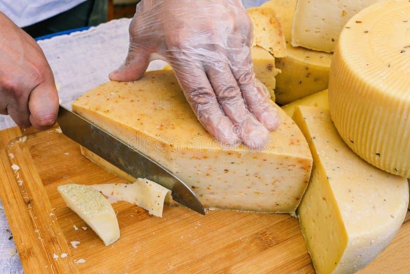 Mann schneidet den Käse auf einem hölzernen Brett Nahaufnahme des Schneidens des Käses Ein Mann schneidet dünne Scheiben des Käse stockfotografie