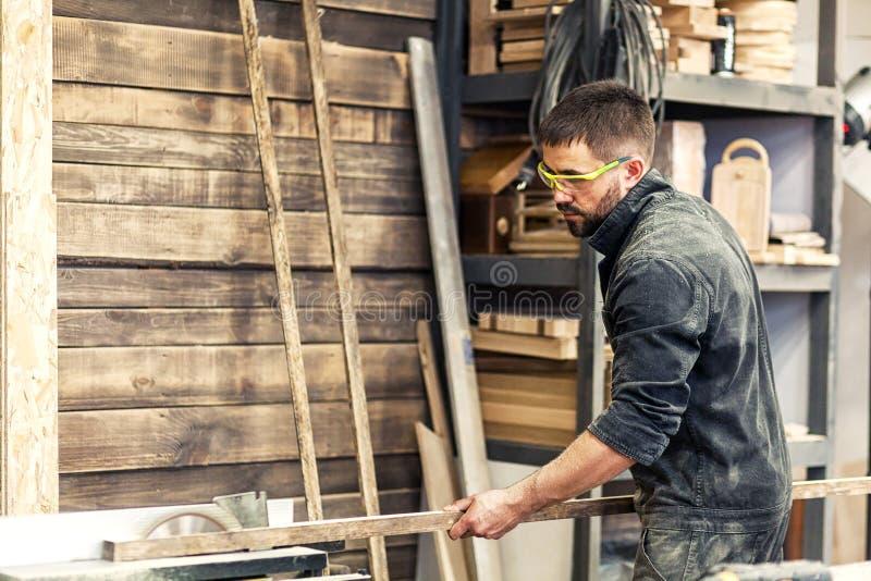 Mann schneidet hölzernes auf einer Kreissäge stockbild