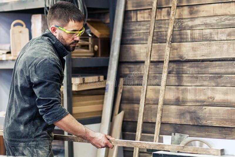 Mann schneidet hölzernes auf einer Kreissäge lizenzfreies stockbild