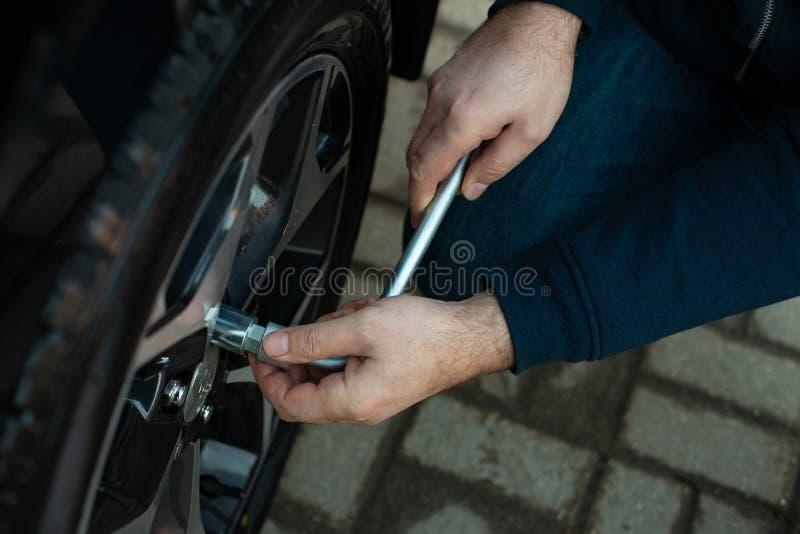 Mann schrauben die Nüsse ab, um Rad abzumontieren stockbilder