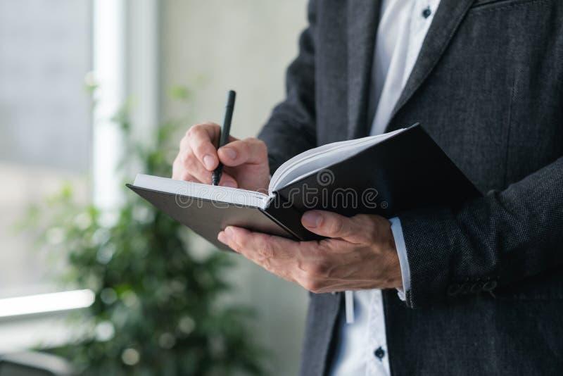Mann schreiben Notizblocktagesordnungszeitplan geschäftliche Angelegenheit lizenzfreie stockbilder