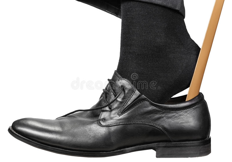 Mann setzt an schwarzen Schuh mit dem lokalisierten Schuhlöffel stockfoto