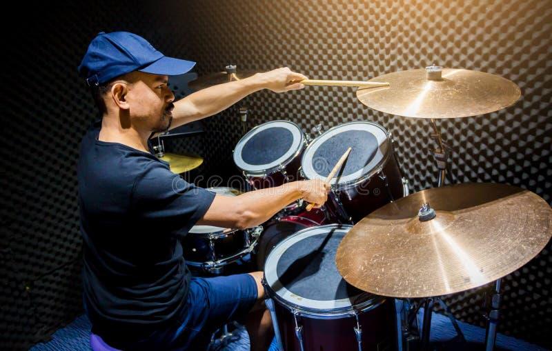 Mann setzte schwarzes T-Shirt zum Spielen des Trommelsatzes mit hölzernen Trommelstöcken in Musikraum ein lizenzfreies stockfoto