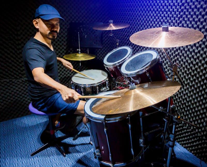 Mann setzte schwarzes T-Shirt zum Spielen des Trommelsatzes mit hölzernen Trommelstöcken in Musikraum ein lizenzfreie stockfotografie