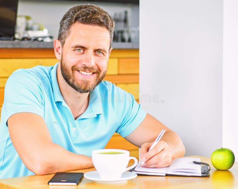 Mann sitzen essen grüne Apfelfrucht Kaffee- und Fruchtnachladenenergiereserve Gesunde Gewohnheiten Gesundes Mannsorgfaltvitamin stockbild