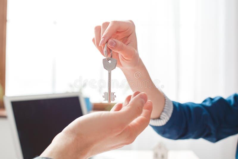 Mann am sitzenden Mittel der Immobilienagentur, das Schlüssel zur Kundennahaufnahme gibt stockfoto