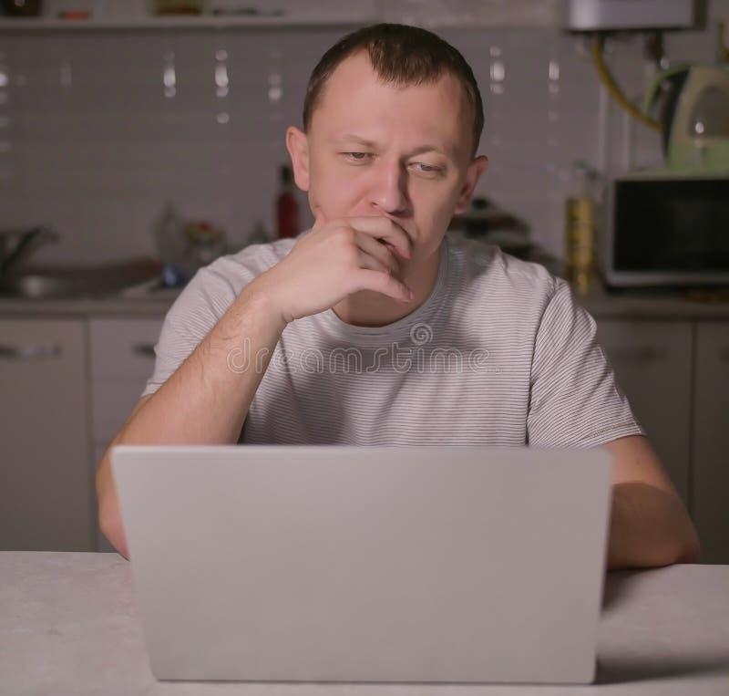 Mann sitzt am Abend in der K?che mit einem Laptop stockfoto